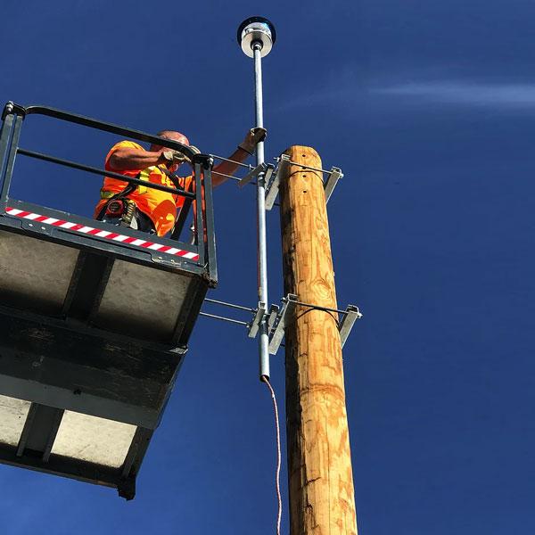 worker installing a EMP pole